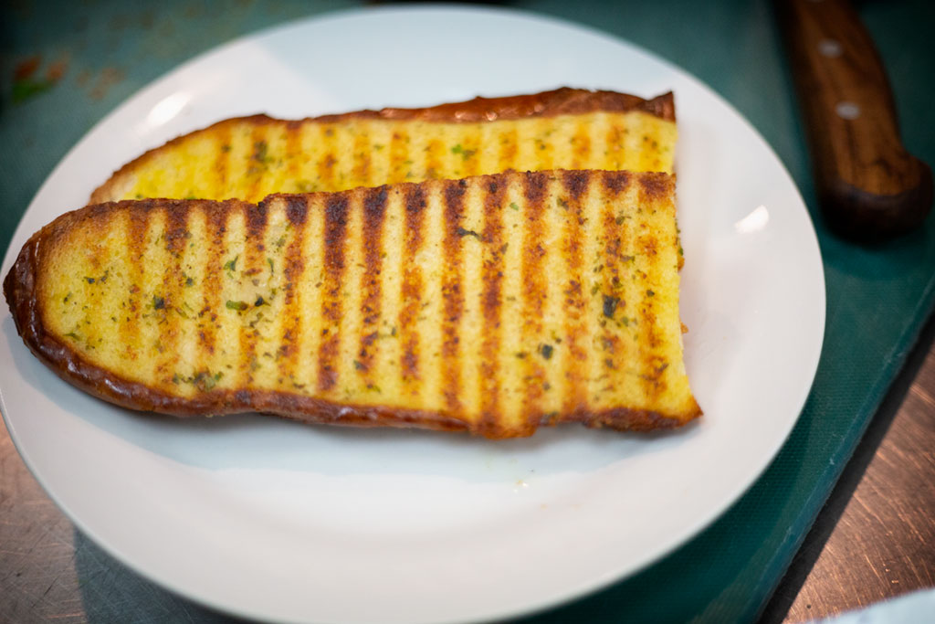 Grilled sliced bread brushed with garlic & herb oil